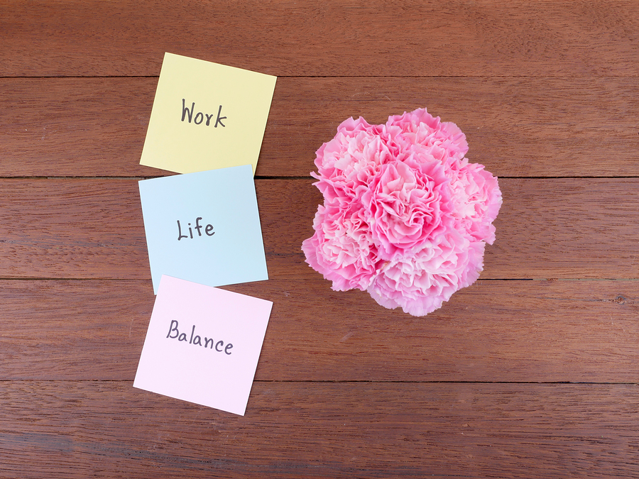 Post it notes saying Work, Life, Balance and flowers in vase