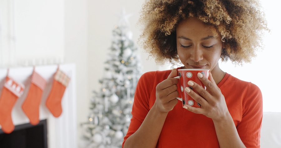 Pretty woman drinking coffee in front of Christmas tree